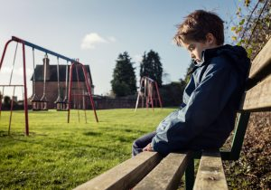 Upset problem child sitting on play park playground bench concep